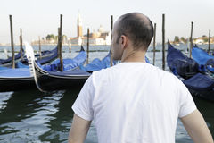 Man enjoying the view of the gondolas. At St. Marks Square in the background the church and monastery of San Giorgio Maggiore, Venice, Italy Royalty Free Stock Image