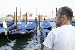 Man enjoying the view of the gondolas, Venice, Italy. Man enjoying the view of the gondolas at St. Marks Square in the background the church and monastery of San Royalty Free Stock Photo