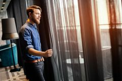 Man enjoying view from luxurious hotel room. Handsome man enjoying view from luxurious hotel room Royalty Free Stock Images