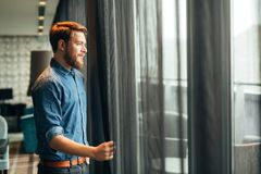 Man enjoying view from luxurious hotel room. Handsome man enjoying view from luxurious hotel room Royalty Free Stock Photo