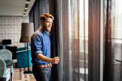 Man enjoying view from luxurious hotel room. Handsome man enjoying view from luxurious hotel room royalty free stock photos