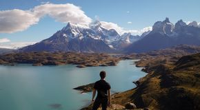 Man enjoying the view from Mirador Pehoe towards the Mountains in Torres del Paine, Patagonia, Chile. View from Mirador Pehoe towards the Mountains in Torres Stock Photos