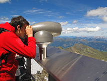 Man enjoying view over mountain range. A young man standing on the top of the Kitzsteinhorn mountain and looking through binoculars over the mountain panorama Stock Image