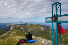 Man enjoying the view on a peak marked by a cross in the mountains Stock Photo