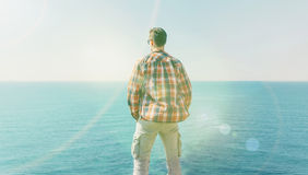 Man enjoying view of sea in summer. Young man enjoying view of sea in summer, rear view. Image with sunlight effect Royalty Free Stock Photography