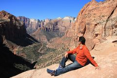 Man Enjoying the View of a Zion National Park. A man sitting on a mountain and enjoying the view of a Zion National Park, located in Utah Stock Photos