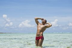 Man enjoying in water on the beach. Expressive Man enjoying in water on the beach Royalty Free Stock Images