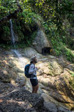 Man enjoying the waterfall and the jungle in Thailand Royalty Free Stock Image