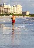 Man enjoys jogging along the beach Stock Image