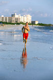 Man enjoys jogging along the beach Royalty Free Stock Images