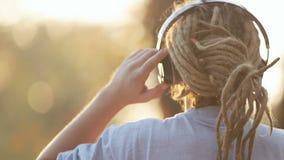 Man Enjoys the Music. Well-built man enjoying the music in big earphones as watching beautiful sunset in urban area on fall evening stock video