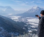 Man enjoys the view and looks down on Garmisch-Partenkirchen and Farchant and takes pictures with his smartphone. A Man enjoys the view and looks down on Royalty Free Stock Photo
