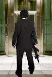 Man entering a business building with a machine gun Stock Photography