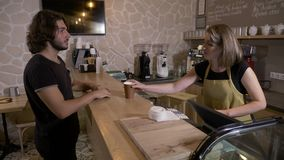 Man entering a coffee shop and ordering a cappuccino to go and then paying it with mobile app crypto currency bitcoin -. Man entering a coffee shop and ordering stock footage
