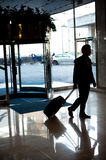 Man entering hotel lobby with his luggage. Car parked in the background Stock Photos