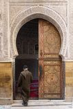 Man entering in a mosque in Fez town of Morocco. Door with beaut Royalty Free Stock Image