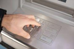 Man entering PIN code on cash machine keypad outdoors. Closeup view stock images