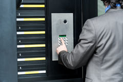 Man entering security code to unlock the door. Businessman entering safe code to unlock the door Royalty Free Stock Image
