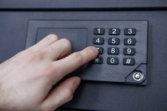 Man enters code from safe close-up. Hand, safe, numbers. Safely store money and jewelry at home. Man enters code from safe close-up. Hand, safe, numbers. Safely Stock Photo