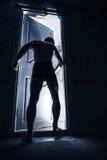 Man enters opening door from black room Stock Image
