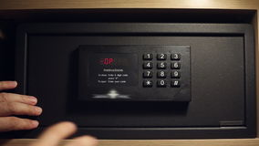 A man gets the money from a safe deposit box. A man enters the secret code and gets the money and valuables from a safe deposit box stock footage