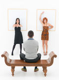 Man entertained by two women in an art gallery Stock Image