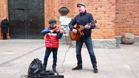 The man is entertaining children with large soap bubbles in the Castle Square of Old Town. Warsaw, Poland - Mart 10 2019: Street musicians father and son stock video footage