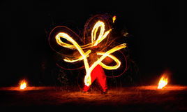 Man entertains audience with the help of fire carrying fire performance night. Stock Images