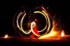 Man entertains with the help of fire, carrying fire performance night. Royalty Free Stock Photo