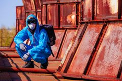 Man environmental mask face pack disguise facemask bitmask protective overall blue orange rast plant factory disused catastrophe. Men in blue protective overall stock photos