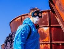 Man environmental mask face pack disguise facemask bitmask protective overall blue orange rast plant factory disused catastrophe. Men in blue protective overall royalty free stock photos