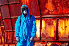 Man environmental mask fire pack disguise facemask bitmask protective overall blue orange rast plant factory disused catastrophe. Men in blue protective overall stock photo