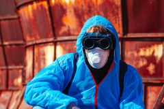 Man environmental mask fire pack disguise facemask bitmask protective overall blue orange rast plant factory disused catastrophe. Men in blue protective overall royalty free stock images