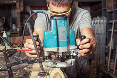 Man equals a wooden plank with a milling machine stock photography