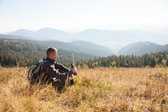 A man with equipment in search of a route in the mountains. A traveler with equipment sits in a dry grass on a mountain ridge stock image
