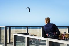 Man equipment surfer stand wind rest blue sun sky sea north. April, 9, 2018. North Sea in The Hague, Scheveningen district, the Netherlands. Man stand on Stock Images