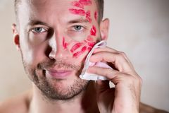 A man erases traces of lipstick from his face with a wet towel