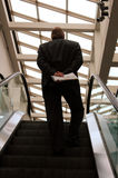 Man on Escalator. A businessman riding up an escalator at Cobo Center, Detroit Stock Photos