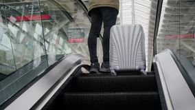 Man on escalator in airport. View from behind of a stylish urban guy with going up on escalator in aiport with his luggage. Man prepared for travelling stock video footage