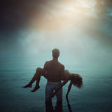 Man in ethereal water with dead lover stock photos