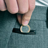 Man with euro coin. A man wearing a suit putting a one euro coin in the coin pocket of his trousers Royalty Free Stock Photo