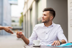 Man with euro money paying for coffee at cafe Stock Image