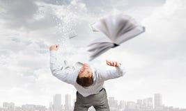 Man evading flying book Royalty Free Stock Photos