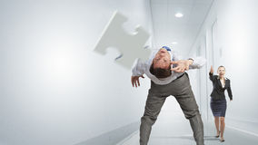 Man evading flying puzzle Royalty Free Stock Images
