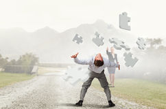 Man evading flying puzzle Royalty Free Stock Photo