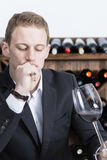Man evaluating a red wine. Thoughtful young man is evaluating a red wine on a wine tasting session holding a red wine glass at a restaurant Stock Image