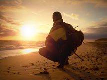 Man at evening sea. Hiker with backpack with hands in pocket along beach. Royalty Free Stock Image