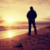 Man at evening sea. Hiker with backpack with hands in pocket along beach. Stock Photos
