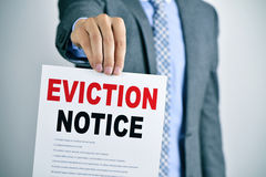 Man with an eviction notice. A young caucasian man wearing a gray suit shows a document with the text eviction notice Royalty Free Stock Photos