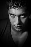 Man with evil scary eyes. Evil man with scary eyes looking from the shadow Stock Photo